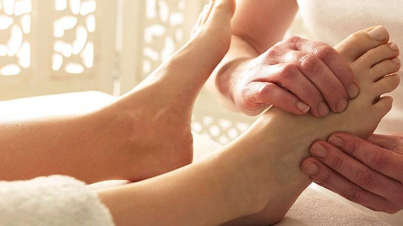 Masajista realiza un masaje de pies