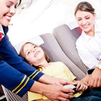 Auxiliar de vuelo abrochando el cinturón de una niña