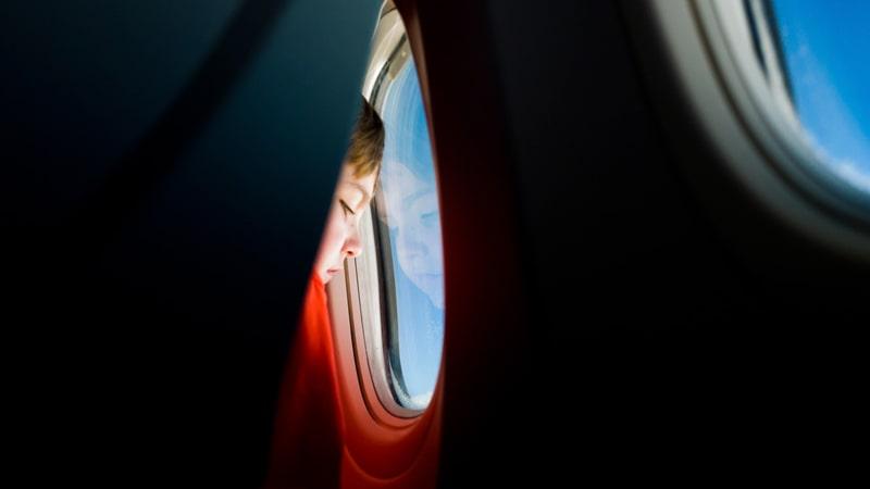 Niño mirando por la ventanilla del avión