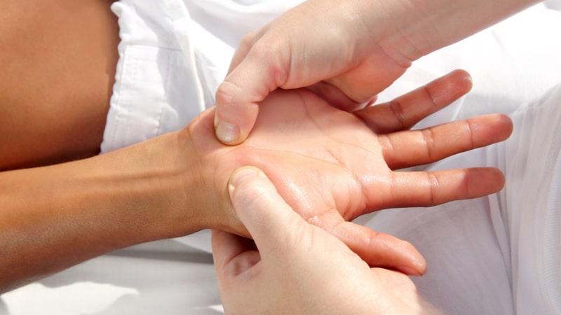 Realizando reflexología de la mano