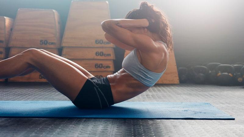 Chica realizando el crunch abdominal