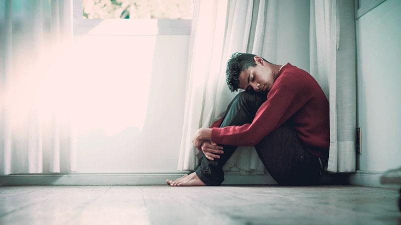 Chico con ansiedad sentado en el suelo