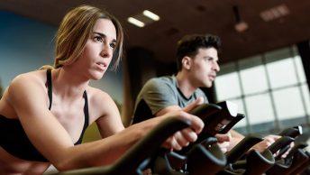 Deportistas pedaleando en ciclo indoor al ritmo de la música