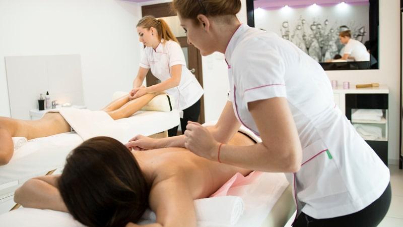 Salón de masajes con dos profesionales trabajando