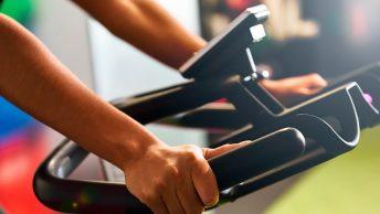 Deportista apoyado en el manillar de bici indoor