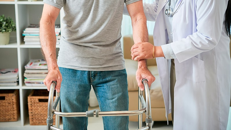 Auxiliar de rehabilitación ayuda a un hombre