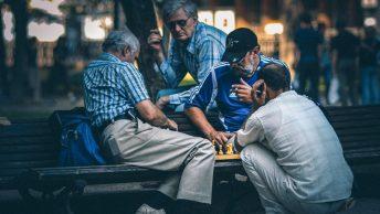 Señores jugando al ajedrez en un jardín