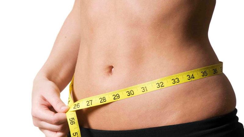 Mujer midiéndose la barriga