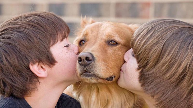 Dos niños besan a un perro