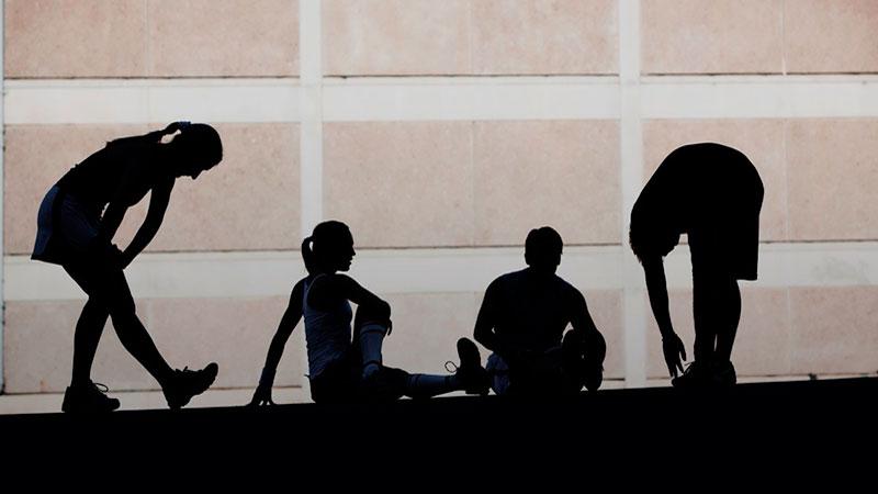 Grupo de atletas estirando después del ejercicio