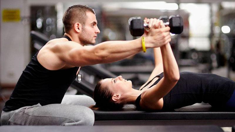 Un entrenador ayuda a subir pesas a una cliente
