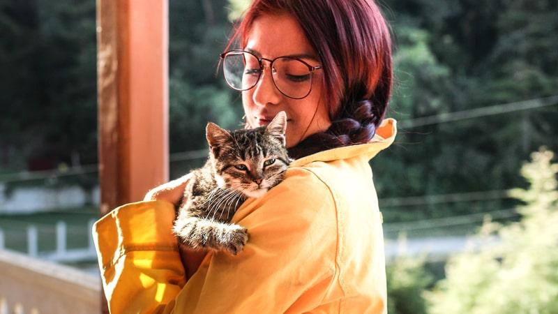 Chica sostiene a un gato en brazos