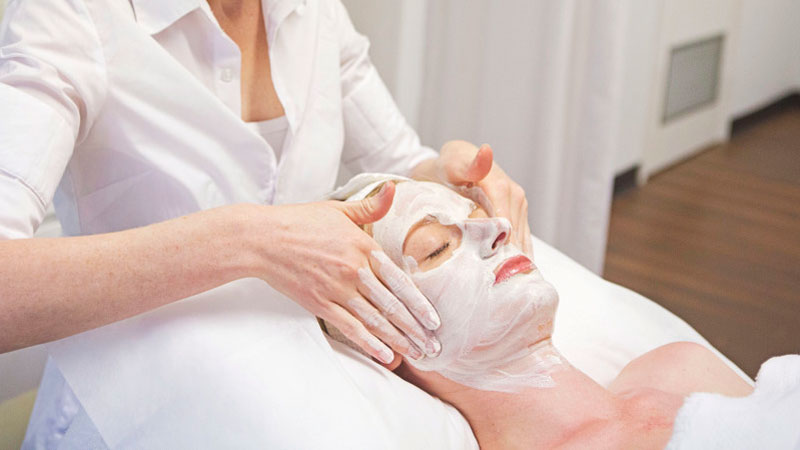Profesional realiza una limpieza facial a una clienta