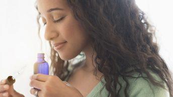 Chica huele el aroma de los aceites esenciales