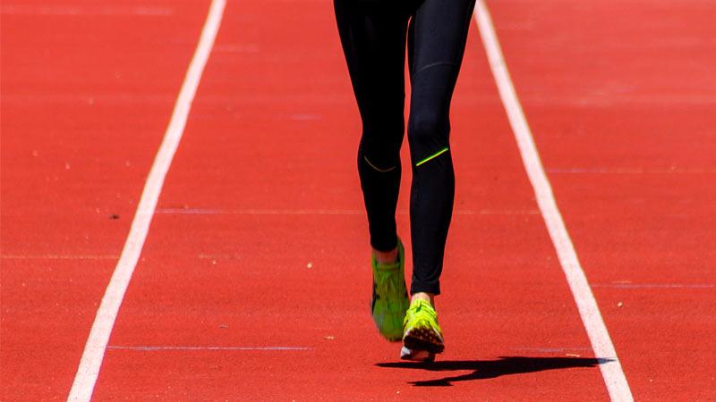 Piernas de corredora en pista de Atletismo