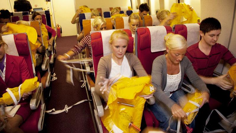Pasajeros de un avión poniéndose el chaleco salvavidas