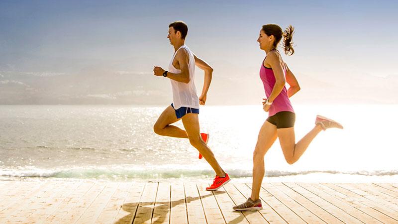 Chico y chica corriendo por la playa