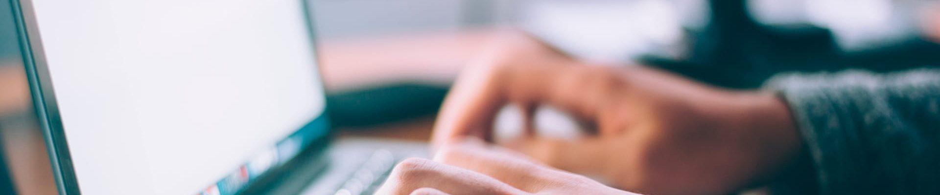 Cabecera del blog de CIM Formación, en la que aparece de fondo una persona tecleando en un ordenador portátil