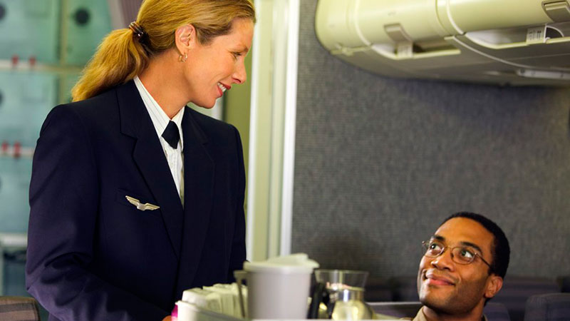 azafata de vuelo atendiendo a pasajero