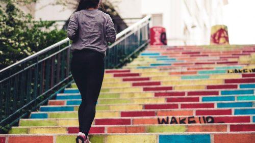 Chica corre subiendo escalera